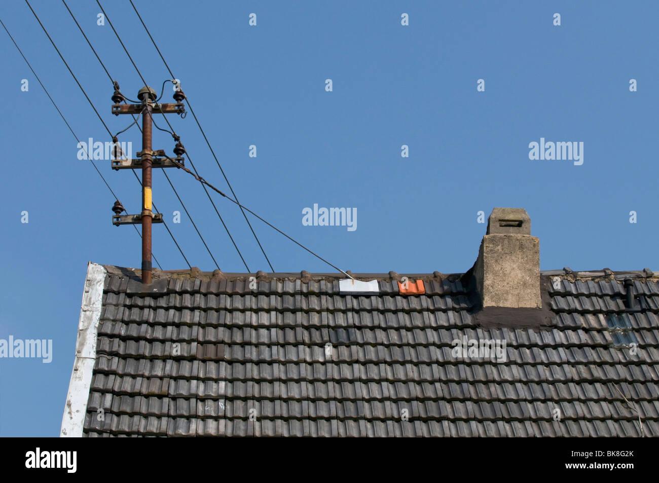 Ancien pouvoir lignes avec isolateurs en céramique sur le toit Photo Stock