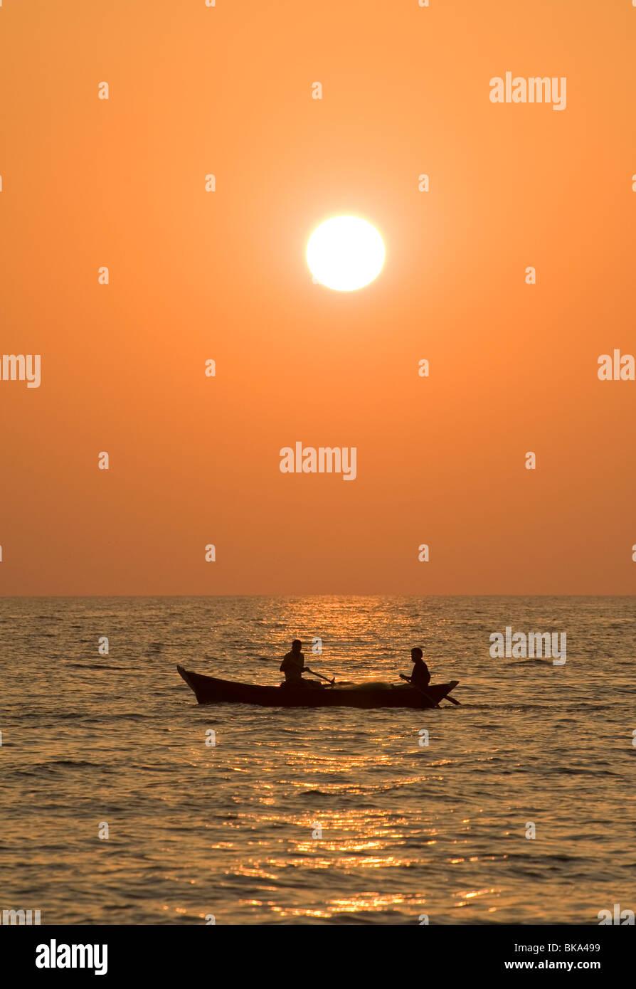 Deux personnes dans un bateau dans la mer au coucher du soleil Photo Stock