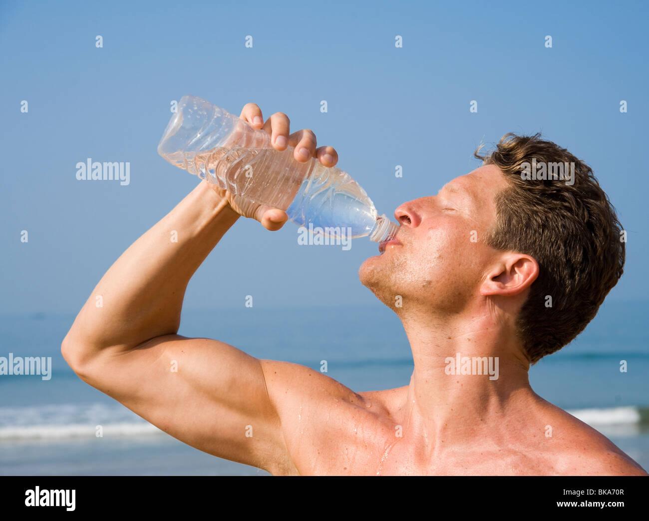 Un homme de boire de l'eau en bouteille sur une plage Photo Stock