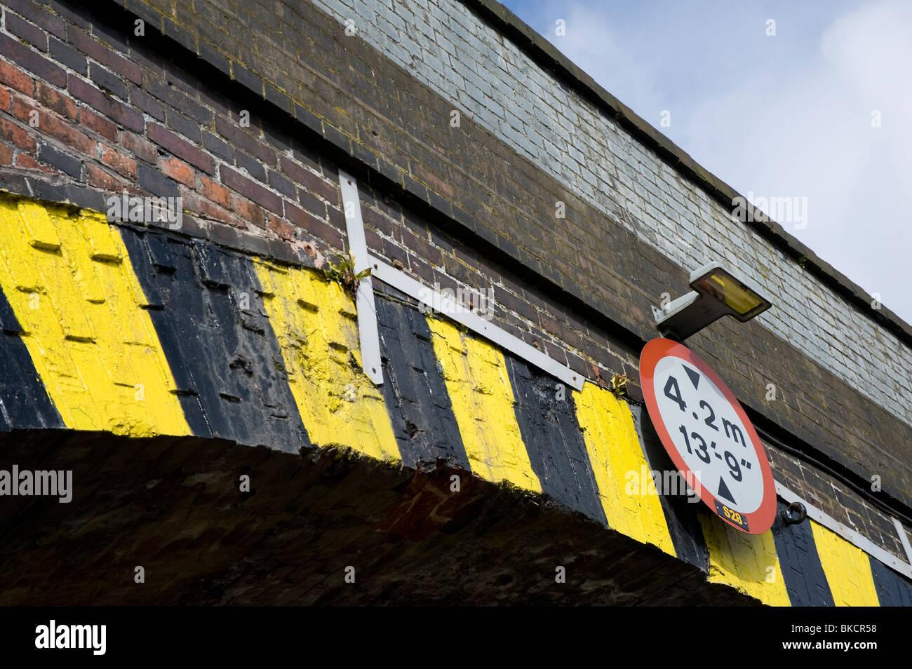 Panneau routier indiquant une limite de hauteur sur un pont de chemin de fer en Angleterre. Photo Stock