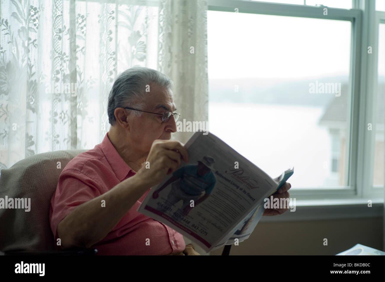Vieil homme est assis dans la salle de séjour fauteuil par fenêtre, lisant le journal. Photo Stock