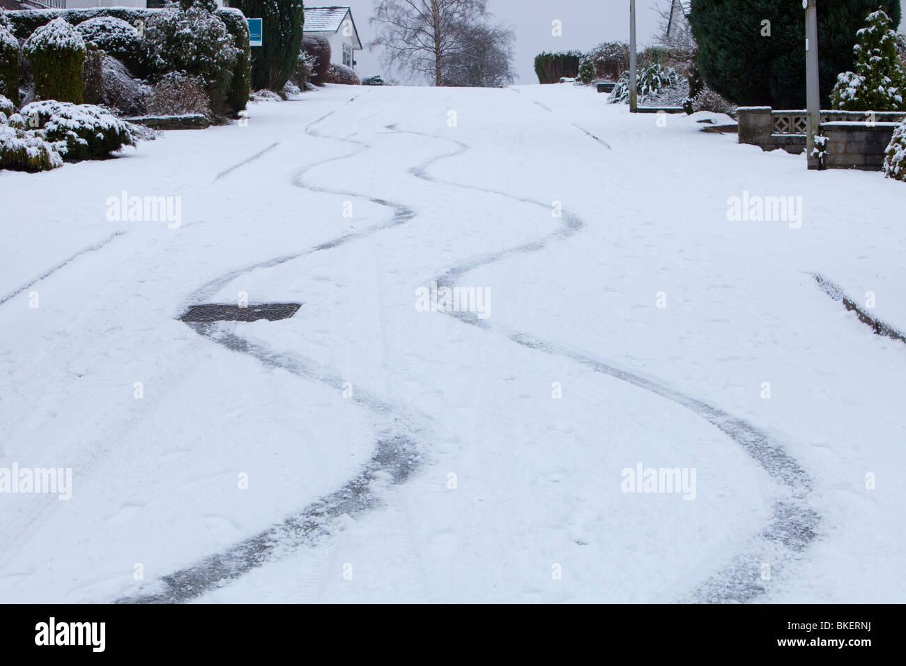 Marques de dérapage dans la neige, d'une voiture sur une route escarpée à Ambleside UK Photo Stock