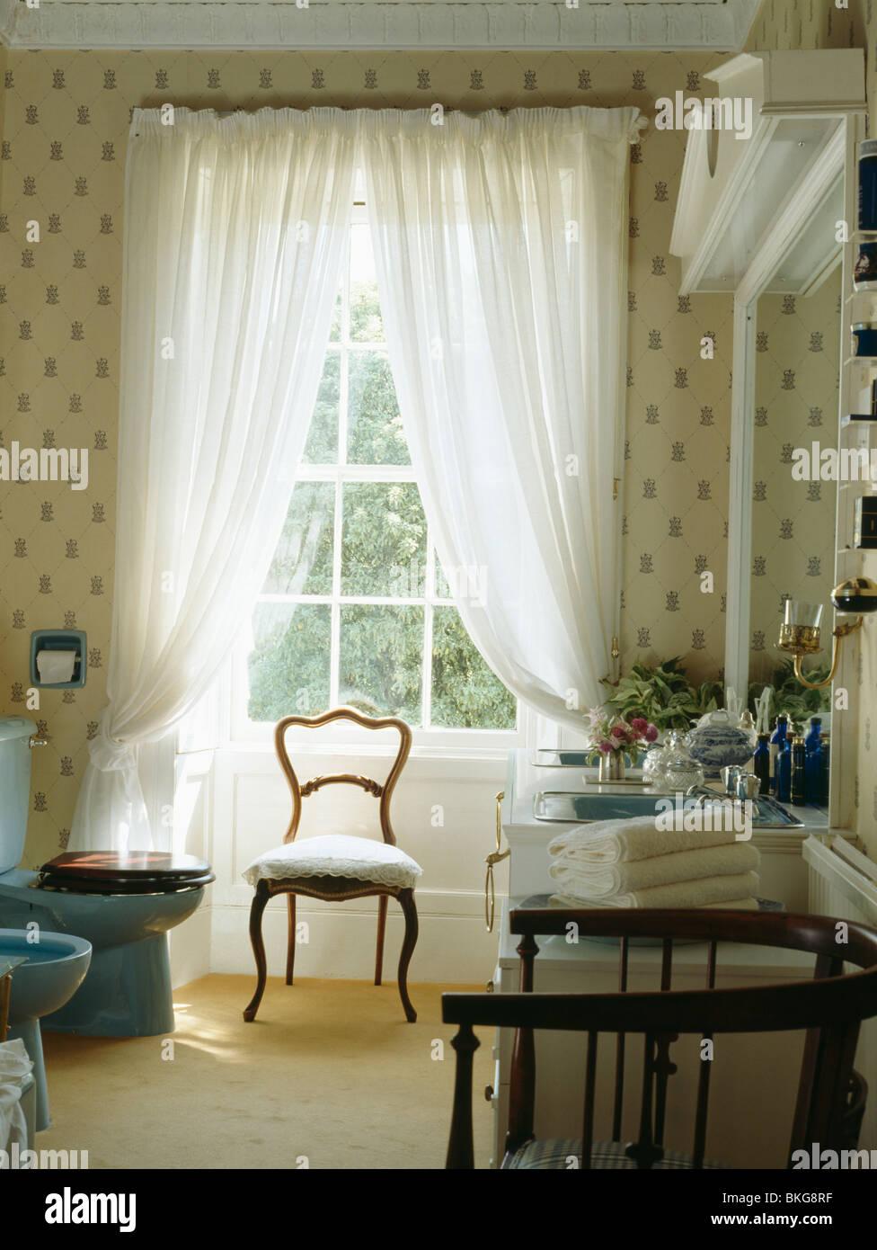 Chaise Face à La Fenêtre Avec Des Rideaux En Voile Blanc Salle De Bain  Traditionnelle Avec Papier Peint à Motifs Et Moquette Crème