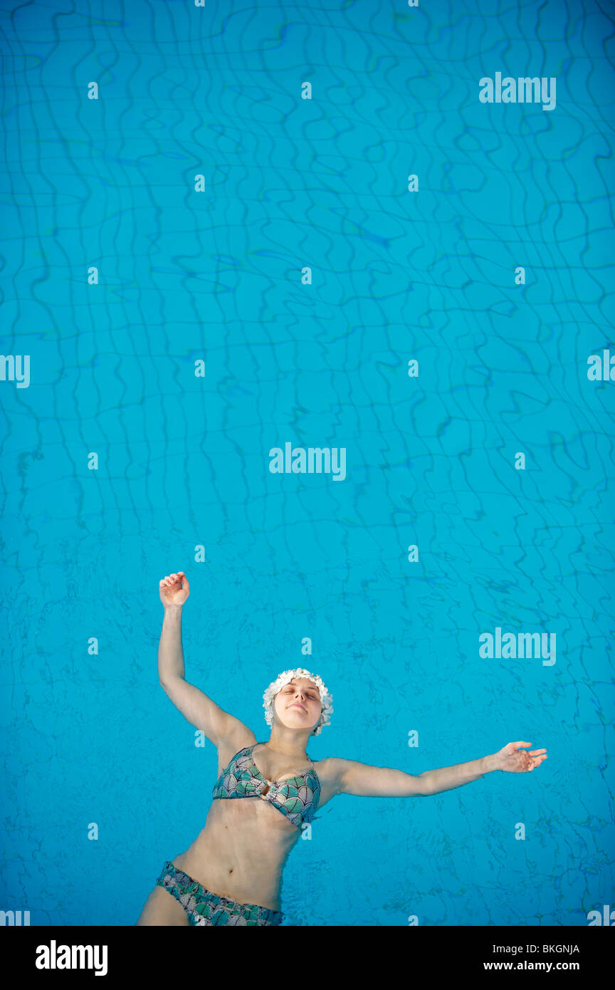 Woman in bikini et la hat flottant dans la piscine bleue d'en haut, les bras tendus. Photo Stock