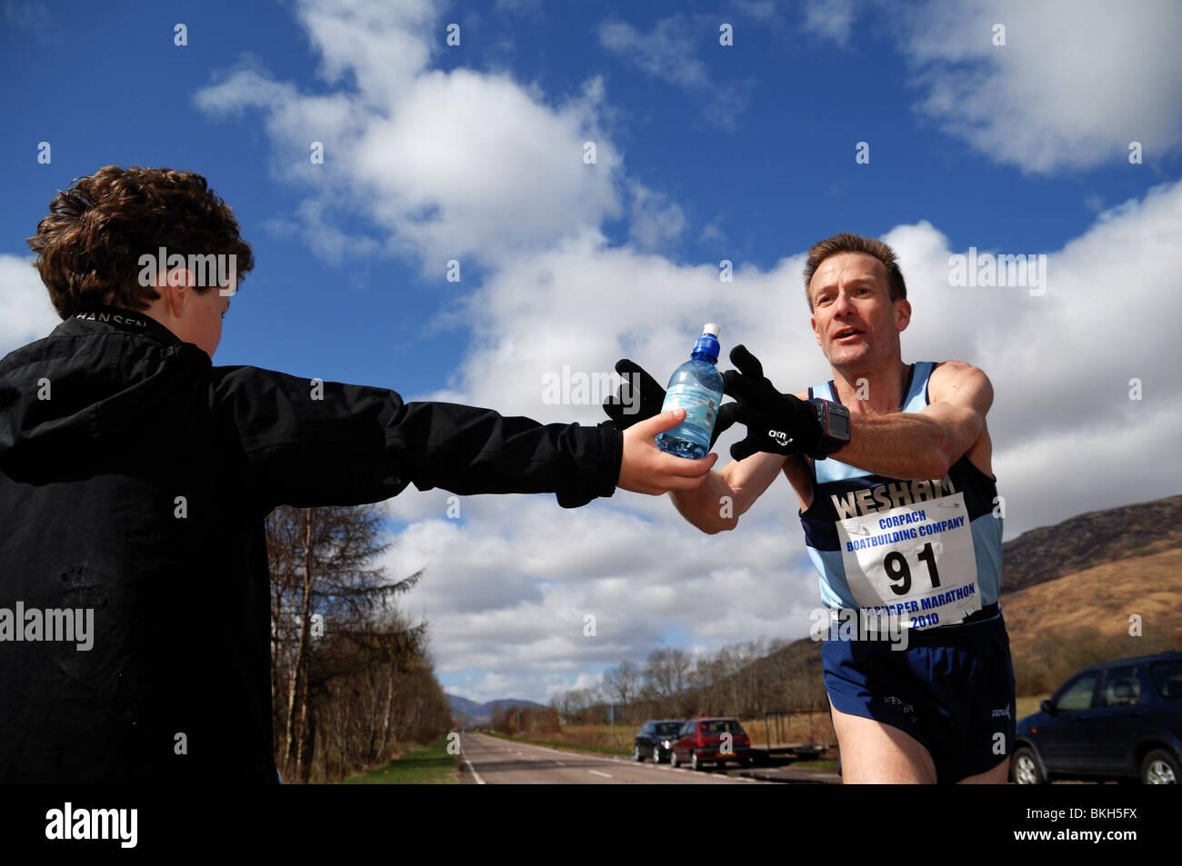 Marathon de Lochaber organisée chaque année par le loch linnie.Runner atteint pour un peu d'eau au cours de la race,de jeune garçon.Sunshine Banque D'Images