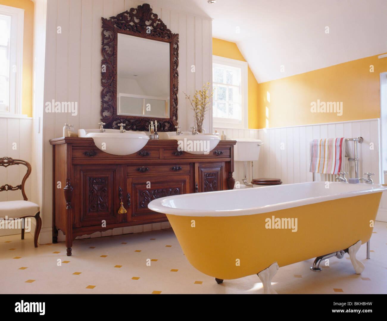 Baignoire jaune en jaune et blanc salle de bains avec un miroir ...
