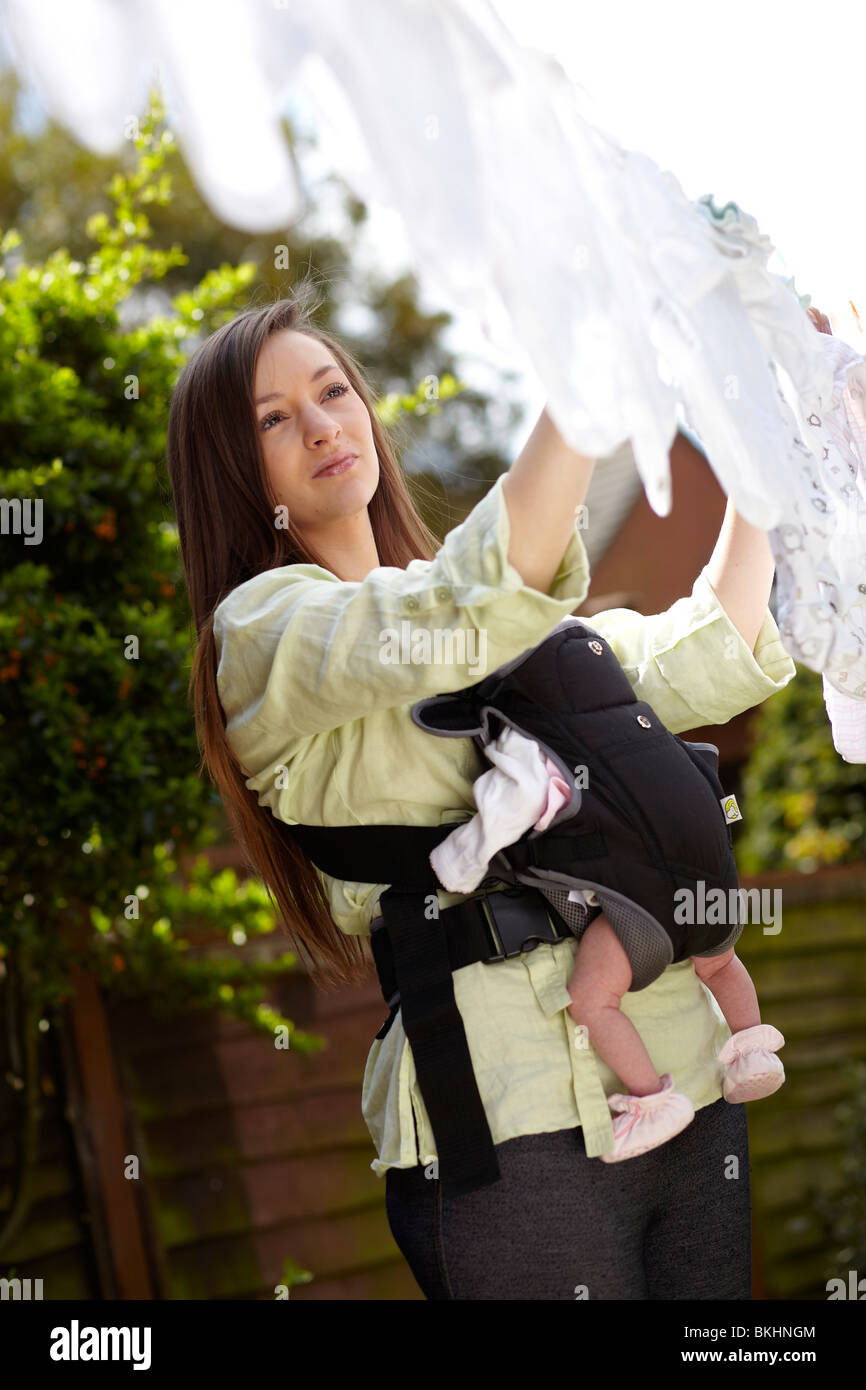 Femme avec bébé en tenant en ligne de lavage Photo Stock