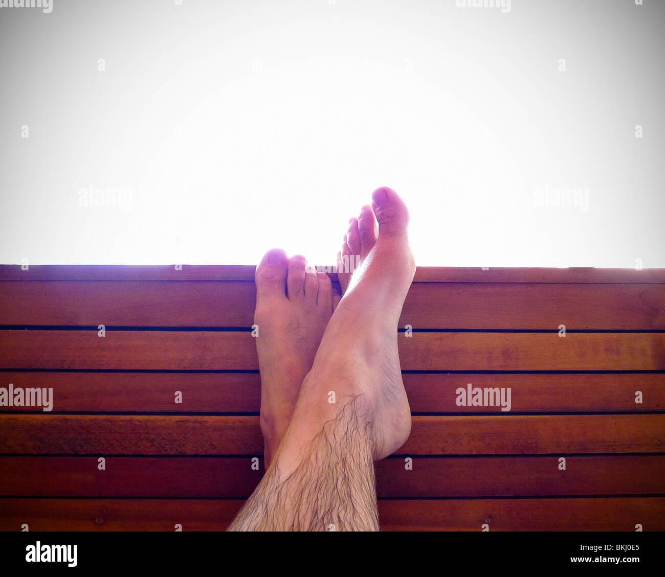 Traversée détendue pieds sur un banc de la station. Photo Stock