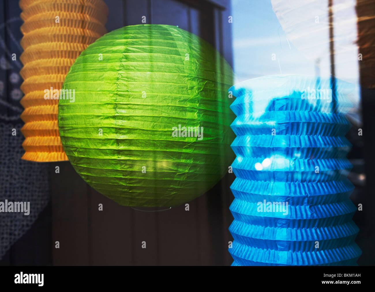 Des lanternes en papier accroché dans shop window Photo Stock