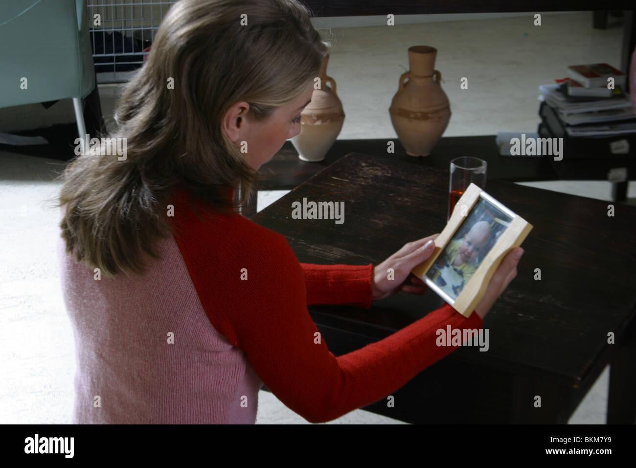 Jeune brunette woman photo dans un cadre et la pensée Banque D'Images