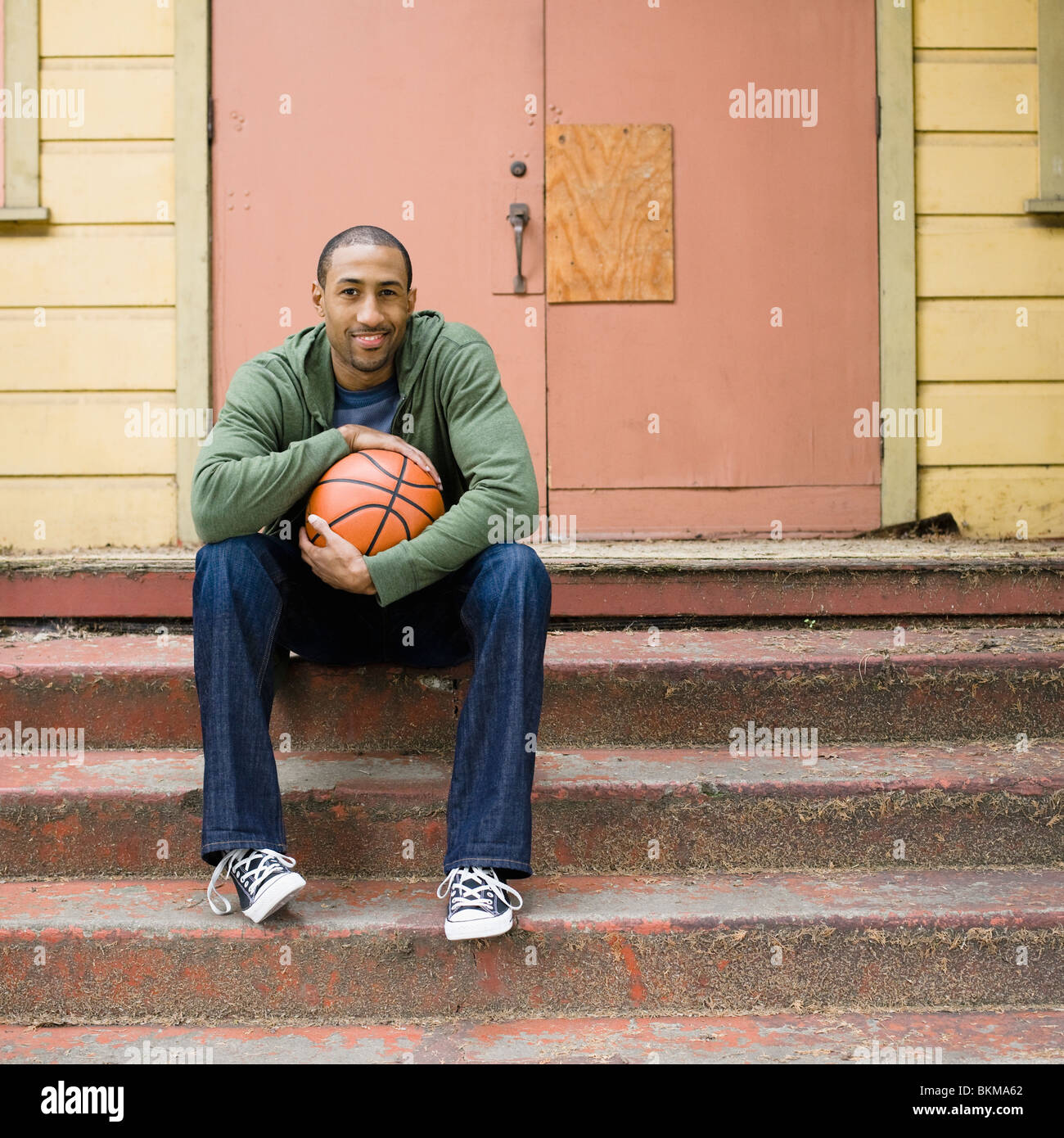 African American man sitting on steps with basketball Banque D'Images