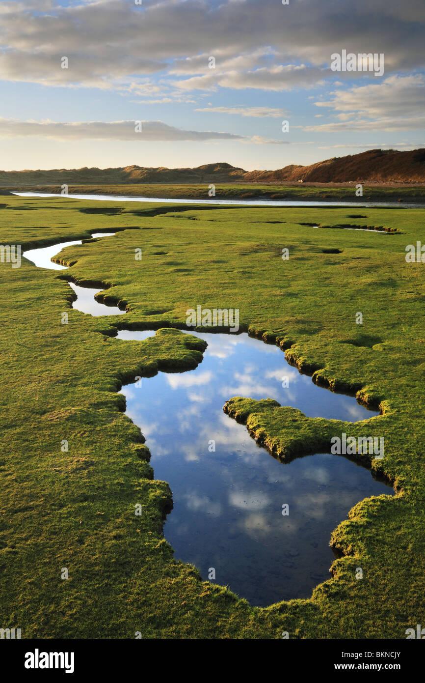 Ciel & nuages reflétée dans l'eau des piscines le long de l'estuaire de Ogmore Vale en Glamorgan, Pays de Galles, Royaume-Uni Banque D'Images