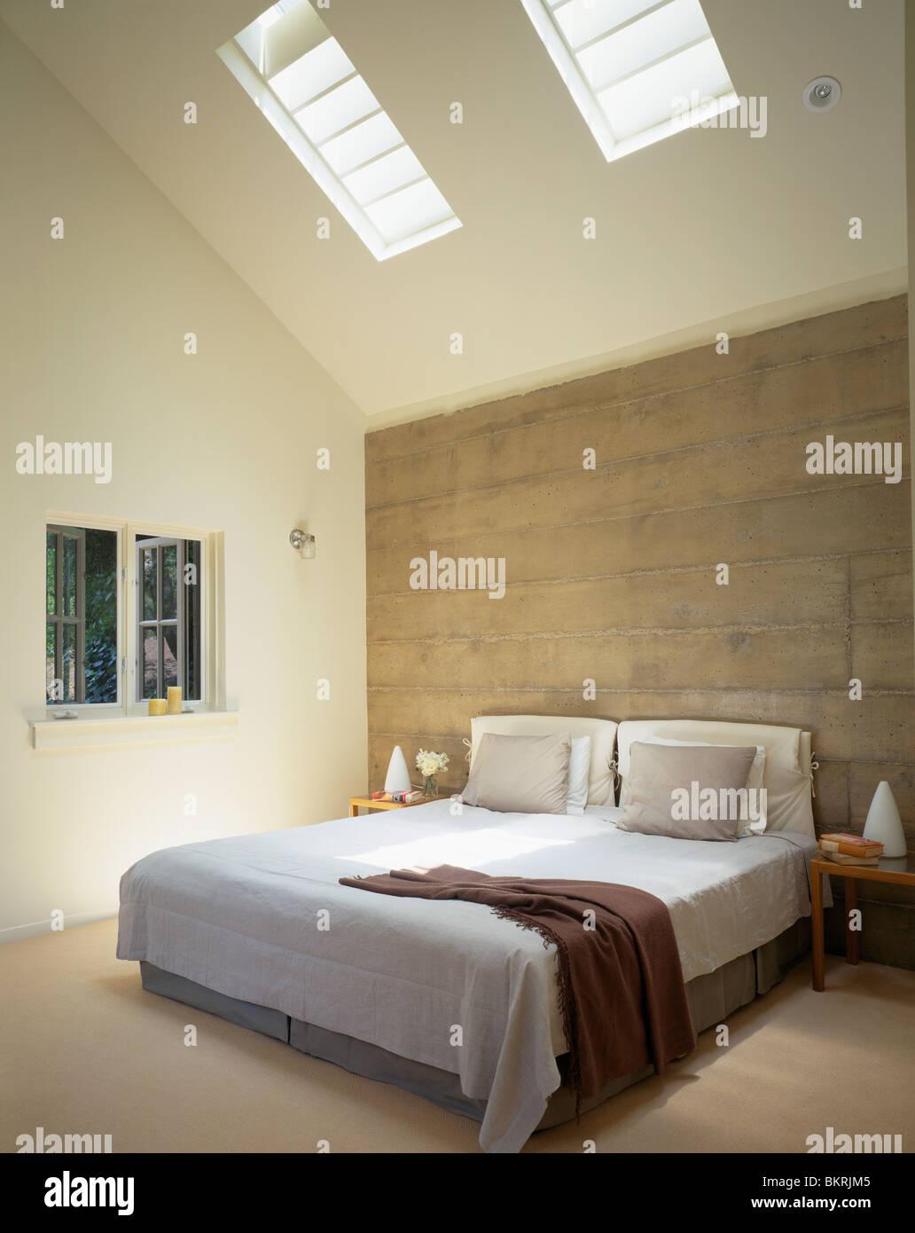 Mur de béton derrière lit avec couverture de lit blanc et gris ...