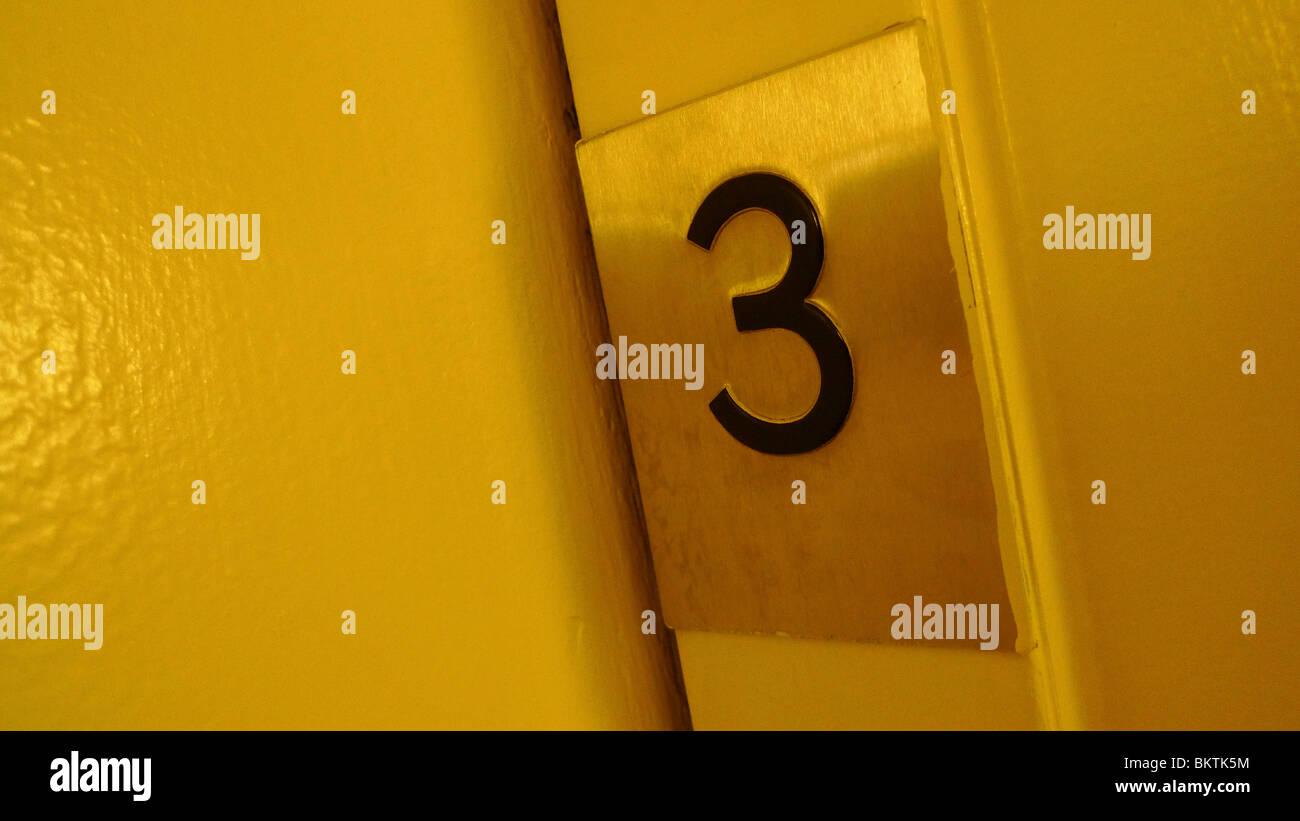 Numéro trois sur une porte de l'ascenseur. Photo Stock