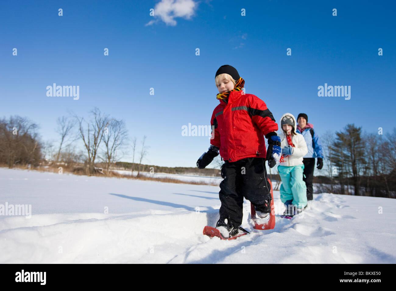 Une femme et son fils et fille de la raquette à travers un champ neigeux au Centre de foresterie urbaine à Photo Stock