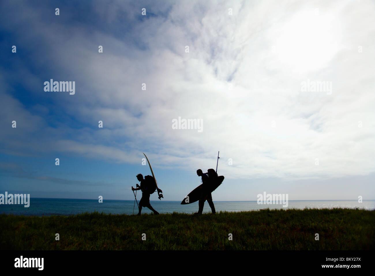Deux hommes randonnée avec des planches sur la Lost Coast, Californie. Photo Stock