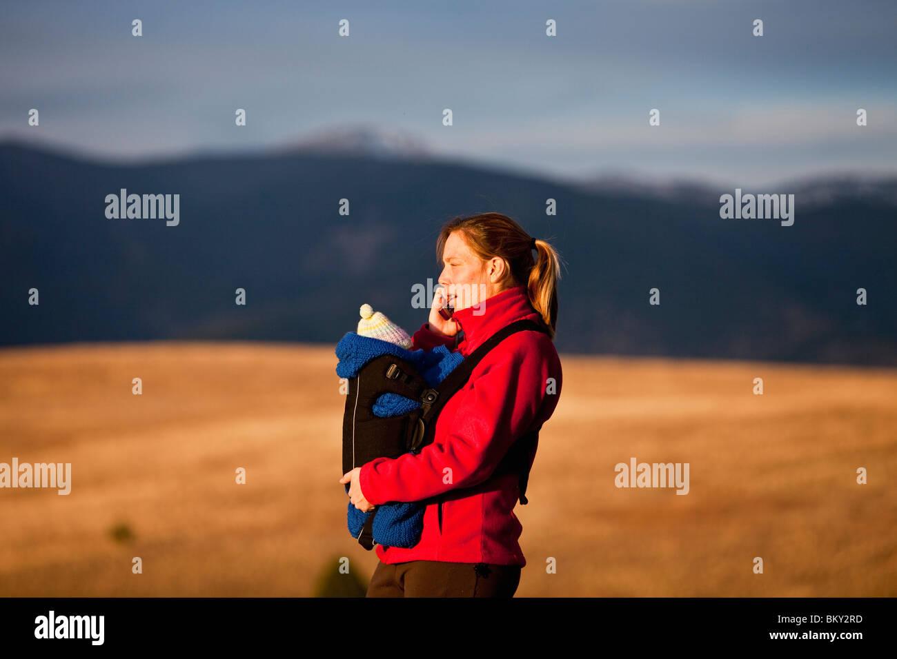 Mère sur téléphone cellulaire et nouveau-né en support avant lors d'une randonnée à Photo Stock