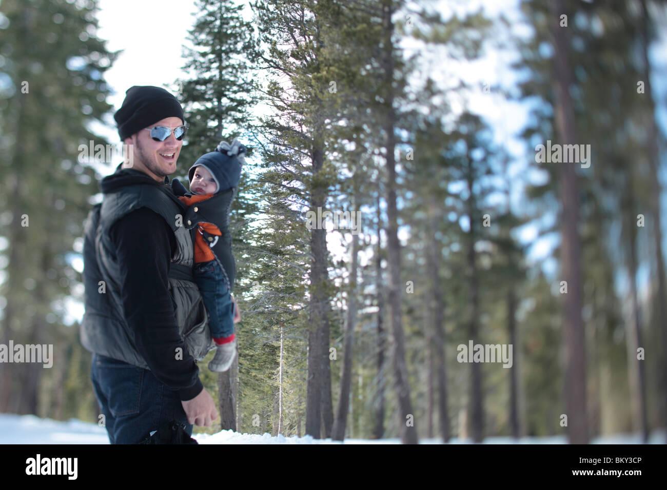 Un père, âgé de 35 ans, marche avec son fils, l'âge de 4 mois, dans le désert couvert de neige du lac Tahoe, Calfornia. Banque D'Images