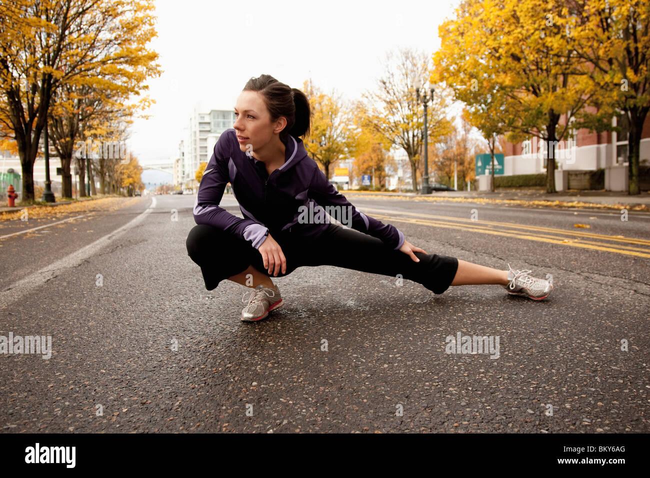 Une femme athlétique dans une veste pourpre s'étendant le long d'une rue déserte à Portland, Photo Stock
