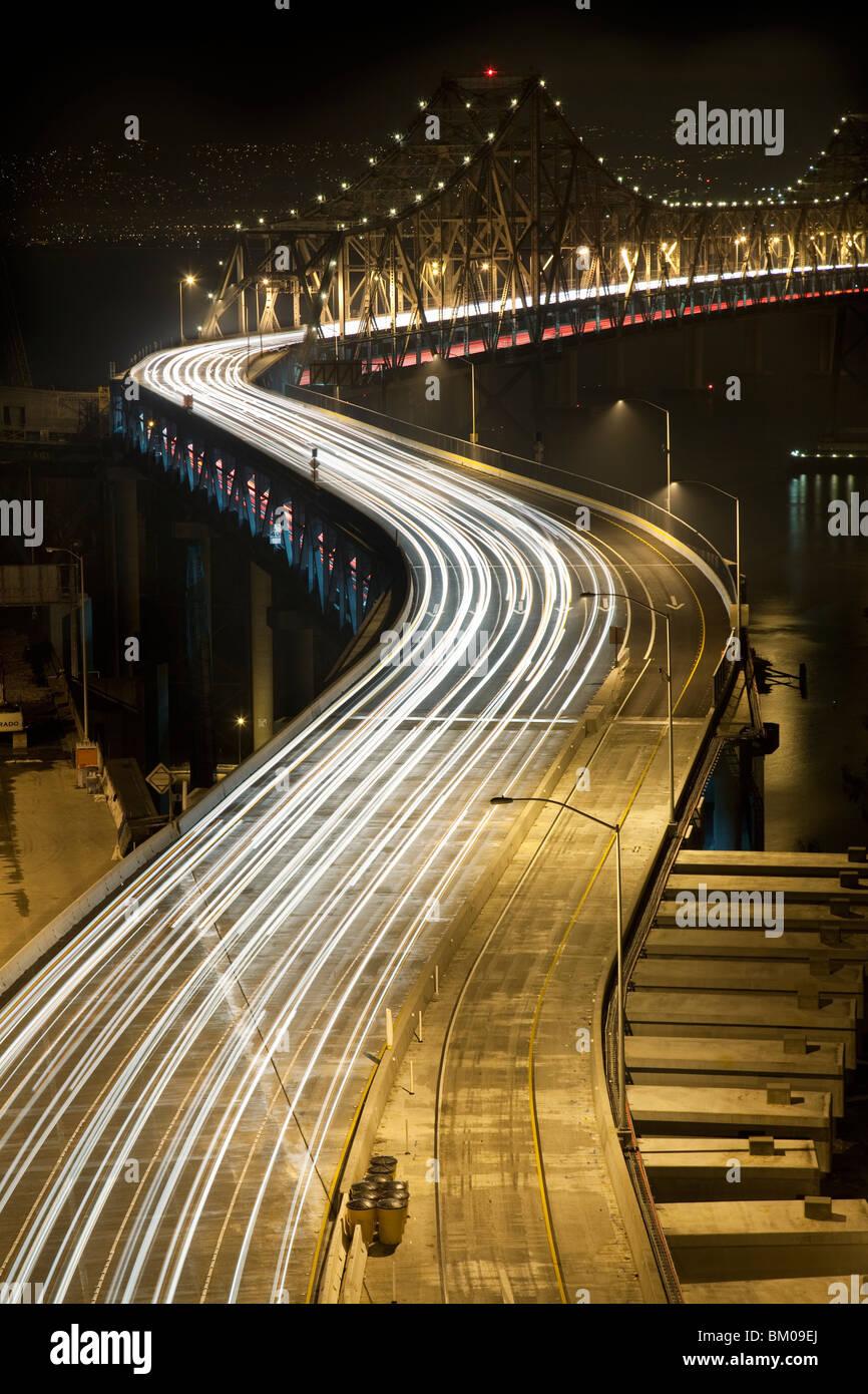Vue de l'Oakland Bay Bridge at night avec circulation Photo Stock