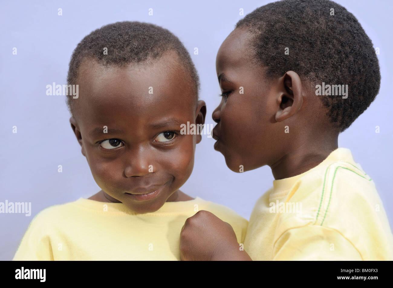 Boy (2-3) chuchotant à l'oreille de son frère jumeau, Le Cap, Province de Western Cape, Afrique du Sud Banque D'Images