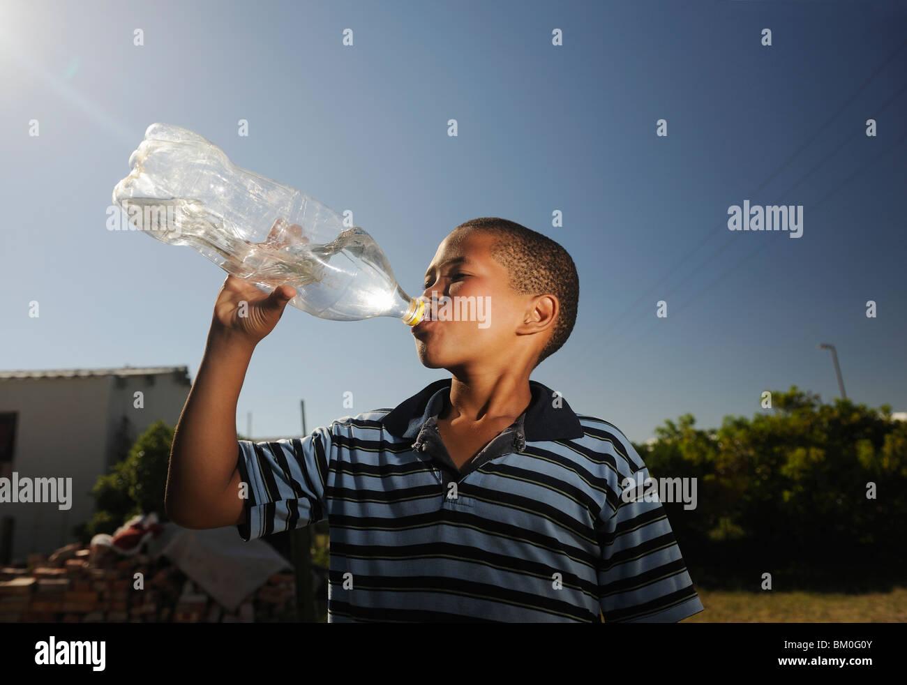 Boy (12-13) l'eau potable de la bouteille en plastique, St Francis Bay, Sea Vista, Province orientale du Cap, Photo Stock