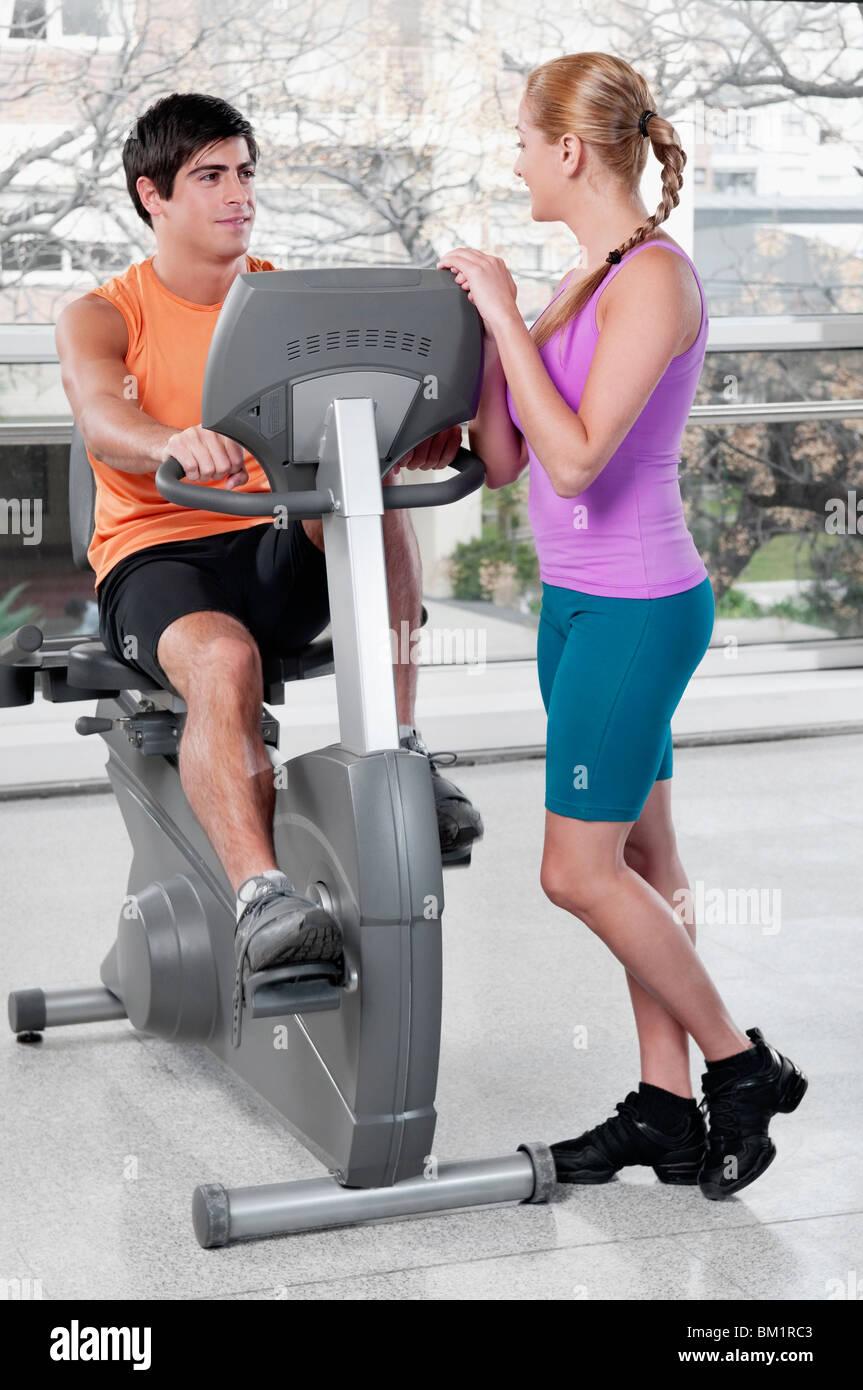 Femme parlant à un homme travaillant sur une machine d'exercice dans une salle de sport Photo Stock