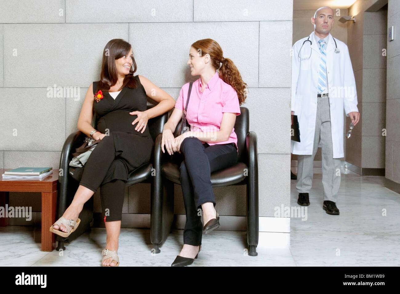 Deux femmes assis dans une salle d'attente de l'hôpital Photo Stock
