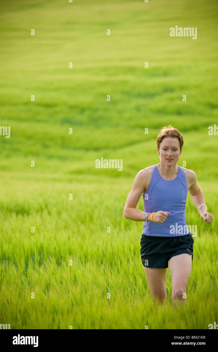 Femme à courir dans un champ de blé, Bozeman, Gallatin County, Montana, USA Photo Stock