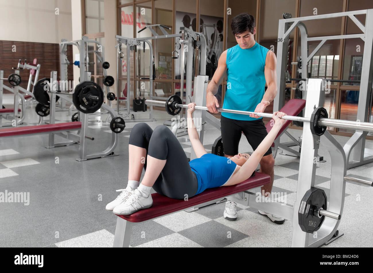 Instructeur d'aider un homme femme dans la formation de poids Photo Stock