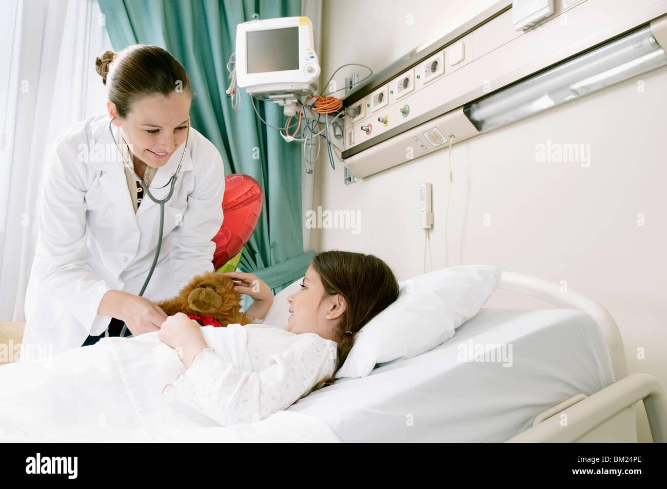 Jeune fille sur un lit d'hôpital en cours d'examen par une femme médecin Photo Stock