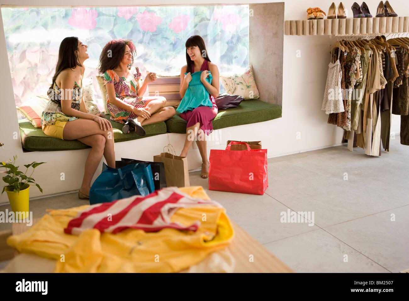 Trois jeunes femmes regardant leurs achats de vêtements dans un magasin Photo Stock
