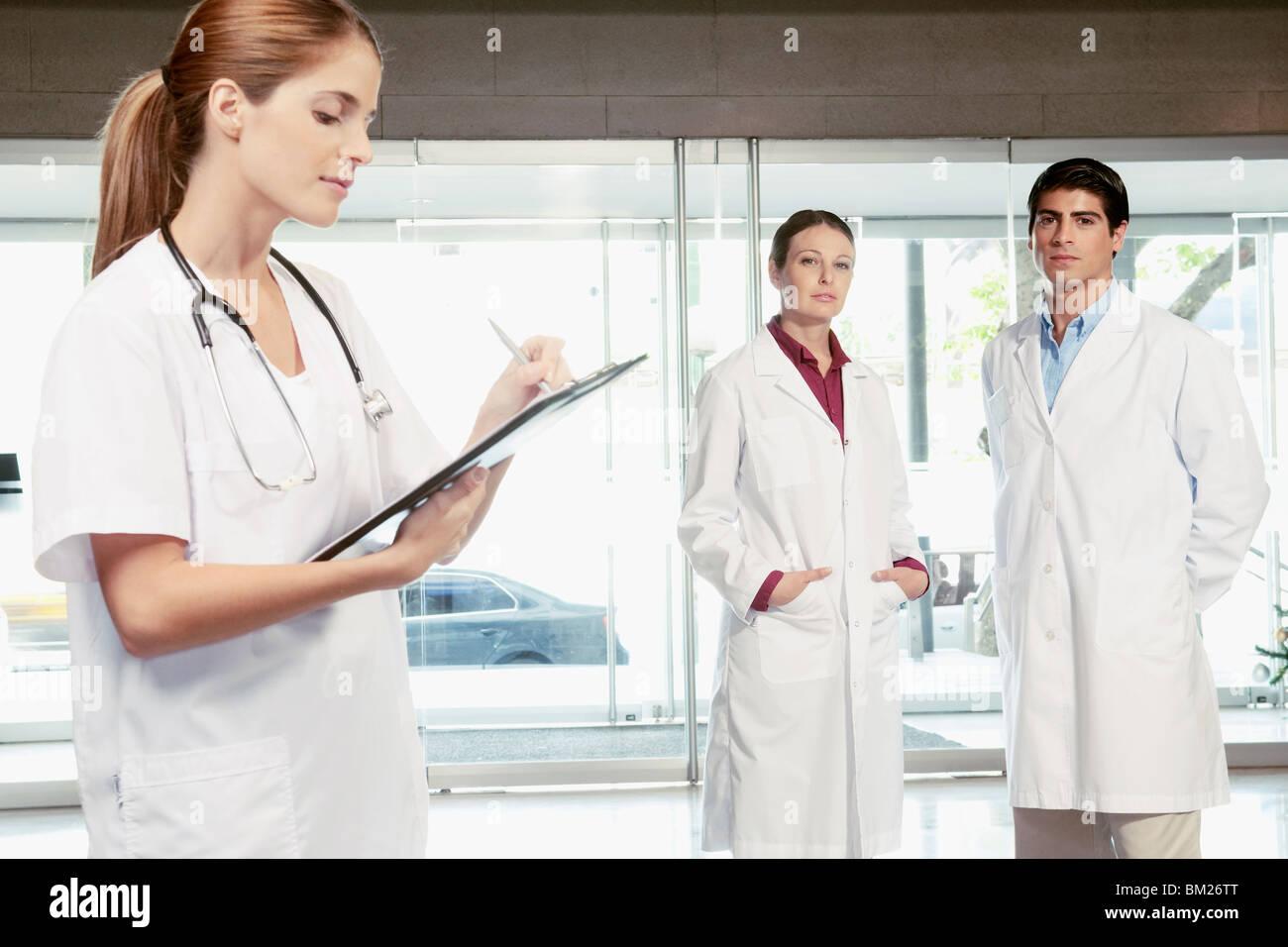 Infirmière écrit sur un presse-papiers avec ses collègues debout dans l'arrière-plan Photo Stock