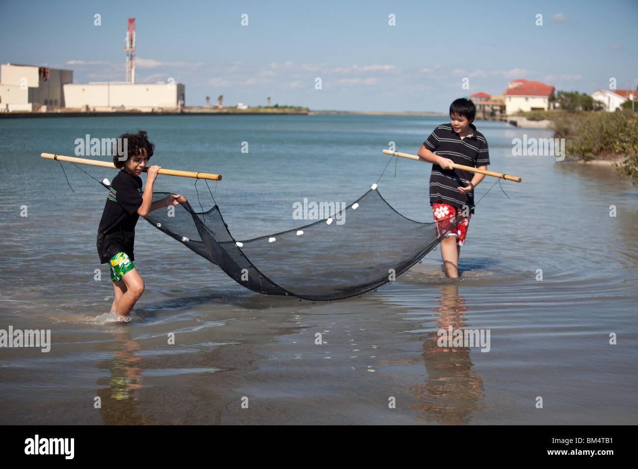 Deux garçons de l'école intermédiaire recueillir la vie végétale et animale de la baie Photo Stock