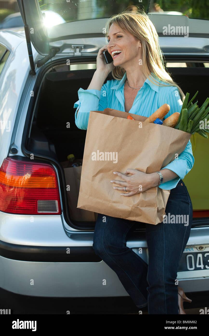 Femme assise en open bicorps avec sac de provisions au tour making phone call Banque D'Images