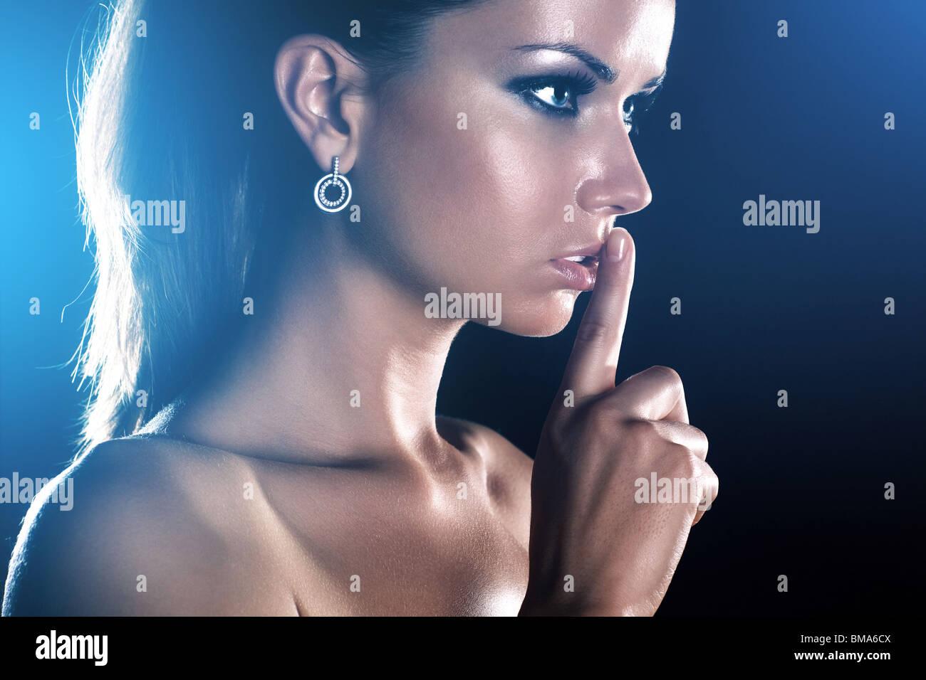 Jeune femme montrant handsign tranquille. Sur fond sombre. Banque D'Images