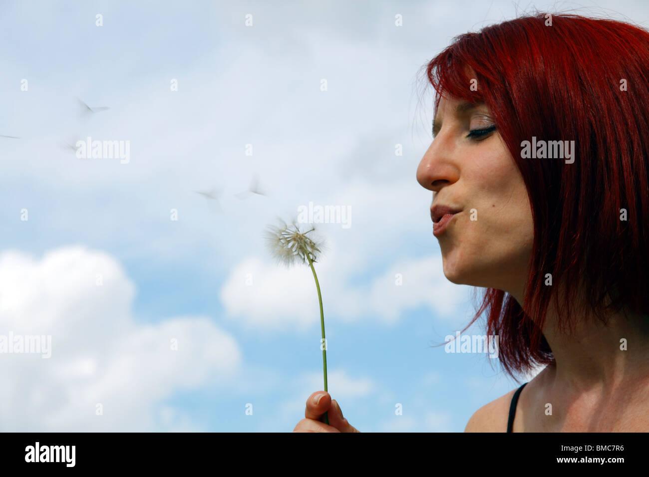 Une femme qui souffle dans un pissenlit. Photo Stock