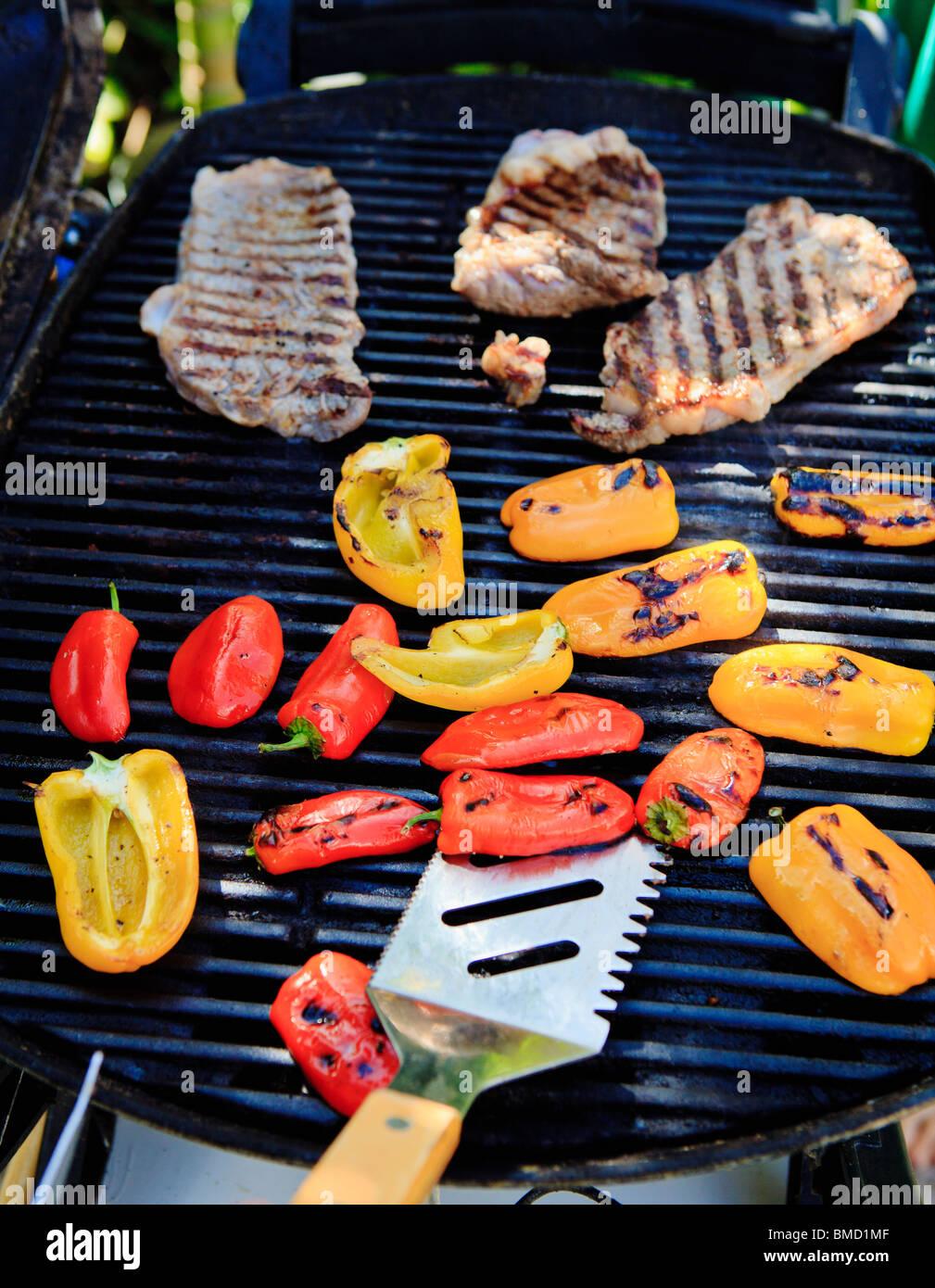 Les steaks et les poivrons sur la grille du barbecue Photo Stock