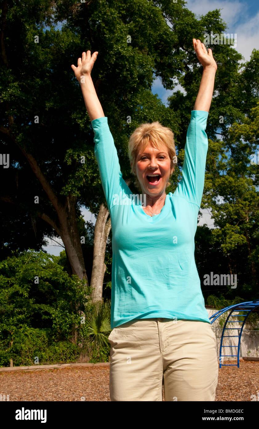 Femme de 60 ans célébrant joyeusement dans la vie en bonne santé à l'extérieur du parc Banque D'Images