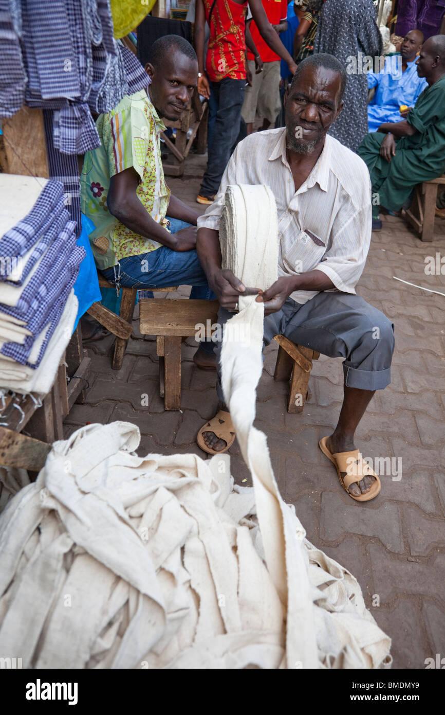Un homme roule longues bandes de tissu en gros rouleaux dans le Grand marché de Bamako, Mali. Banque D'Images
