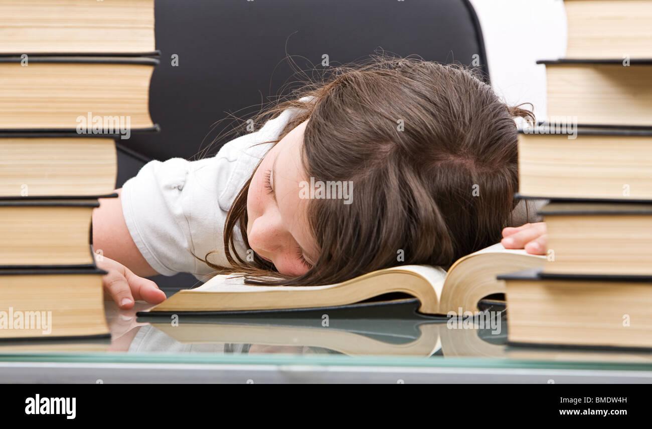 Tourné d'une jeune fille endormie sur ses livres tandis que l'étude Photo Stock