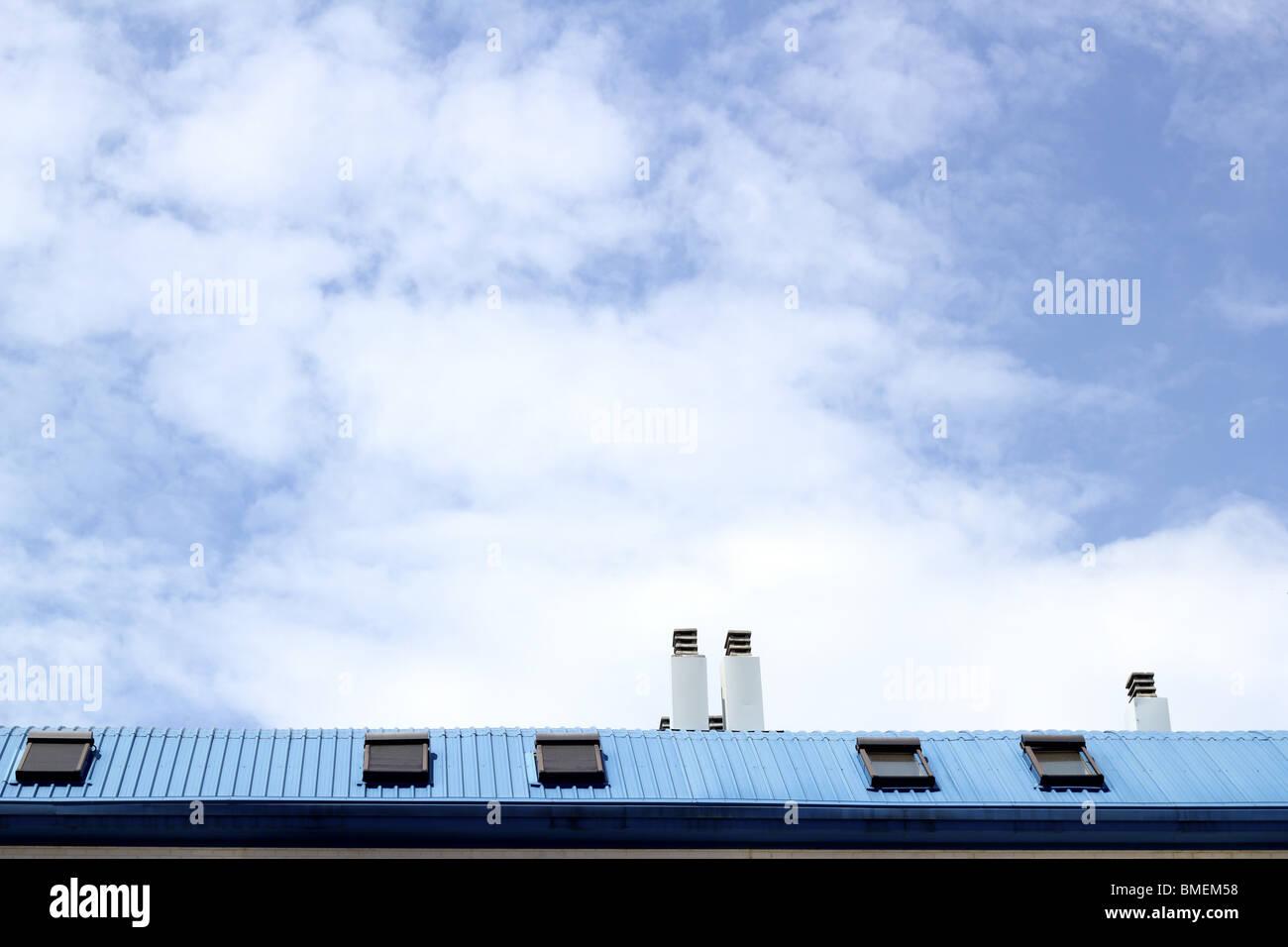 Acier peint bleu lucarne de toit cheminée ciel nuages Photo Stock