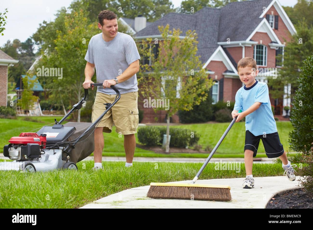 Un père et son fils travaillant dans la cour Photo Stock