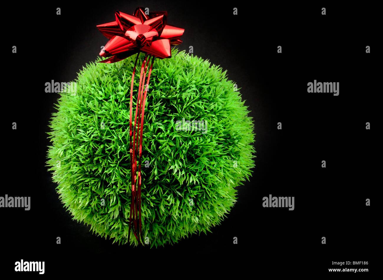 L'herbe verte balle avec arc rouge et ruban au-dessus de lui, un cadeau pour la terre Photo Stock