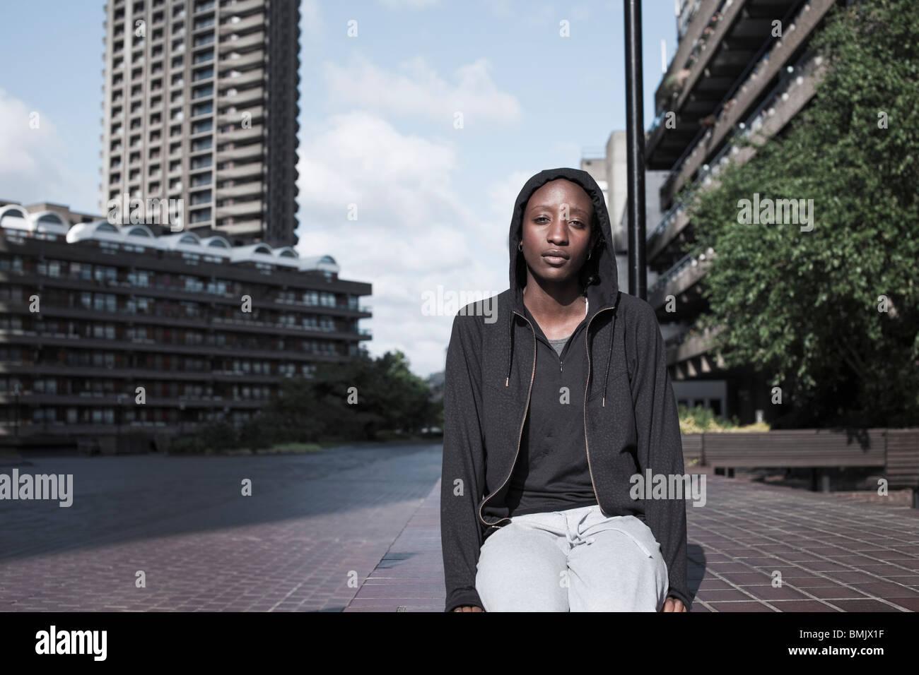 Portrait d'une jeune femme était assise à l'extérieur du City Housing Estate Photo Stock