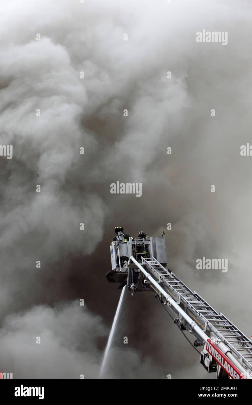 Pompier luttant contre un smoky blaze Banque D'Images