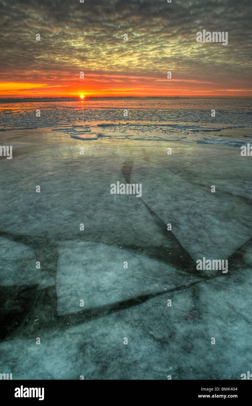 Lever du soleil sur la glace d'un lac d'eau douce dans le Michigan, United States, Amérique du Nord avec des feuilles Banque D'Images