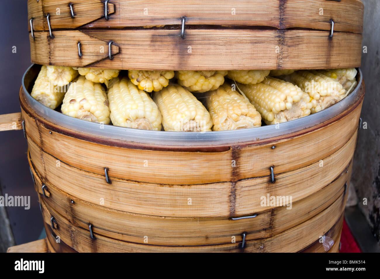 Des épis de maïs dans l'alimentation de rue des paniers de bambou, Shanghai, Chine Photo Stock