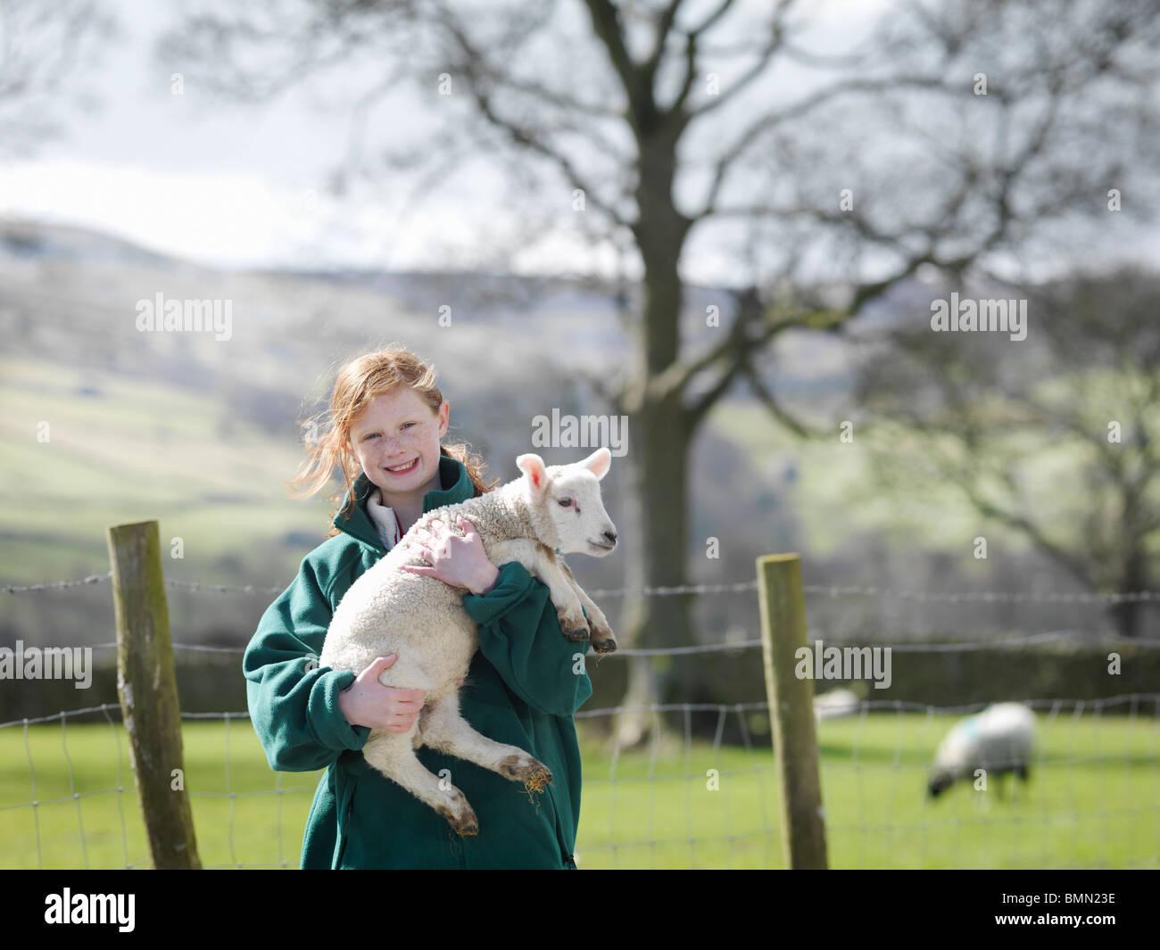 Child holding lamb smiling Photo Stock