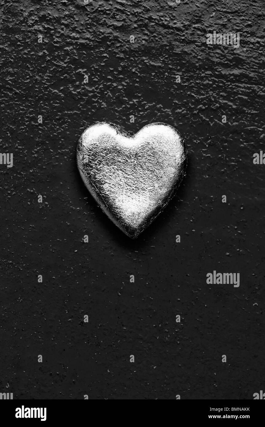 Forme de coeur en or contre metal texturé arrière-plan. Monochrome Photo Stock